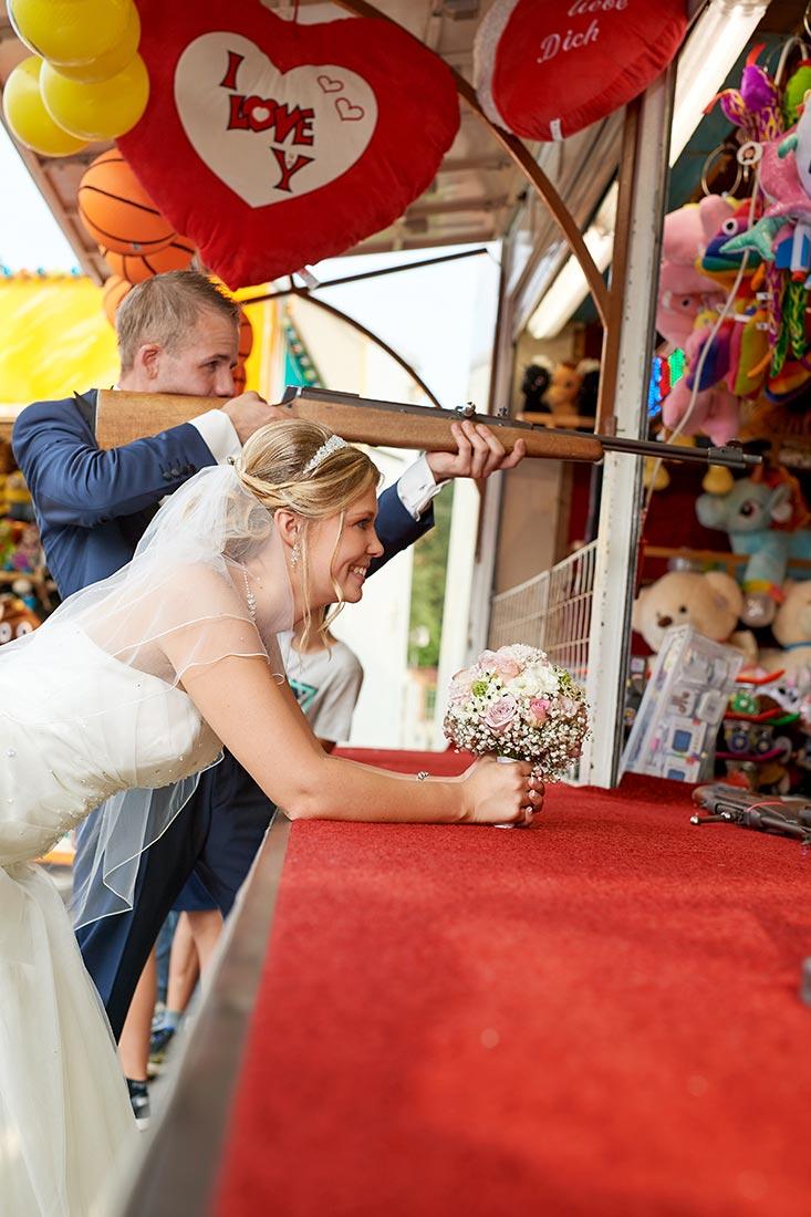 Hochzeitsfotos – Brautpaar an Schießbude auf Kirmes in Staudt